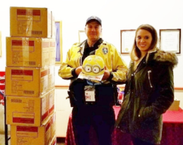 Officer BLaine Hatch with the Juneau Police Department accepts 40 Minion helmets from United Way of Souteast Alaska OFfice Administrator Kaylee MAtheny as a part of the K.I.D.S. distributiuon