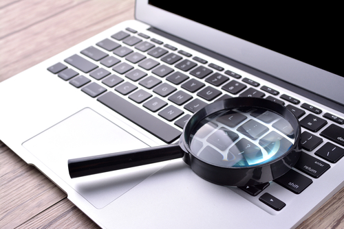 Laptop computer with magnifying glass_ concept of search