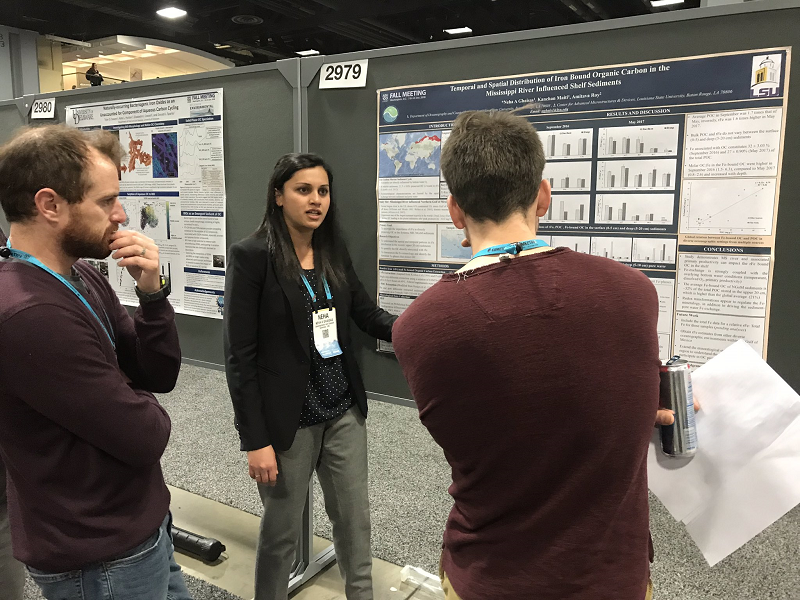 Photo of a student explaining her research poster to two onlookers at the AGU conference