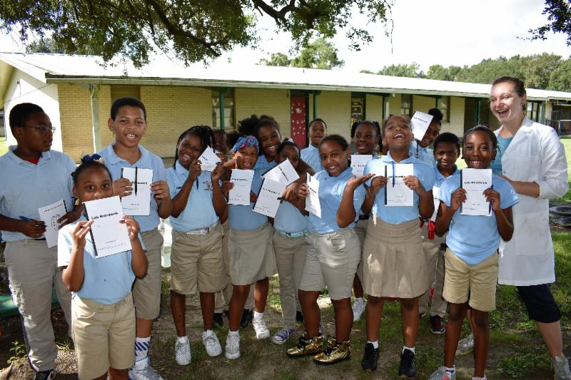 Kendall Valentine and a group of elementary students pose with their very own lab notebooks.