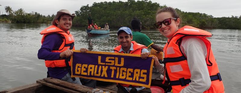 Mario Hernandez and two other researchers on a boat holding a banner that reads: LSU Geaux Tigers.
