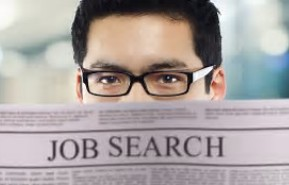 Man looking over newspaper with headline %22Job Search%22