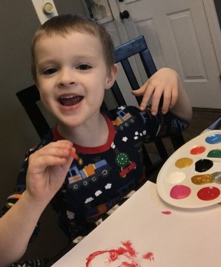 Photo of Trevor playing with fingerpaints