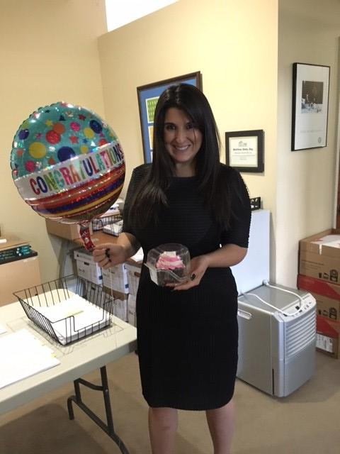 Lisa, standing and holding a mylar balloon and a cupcake.