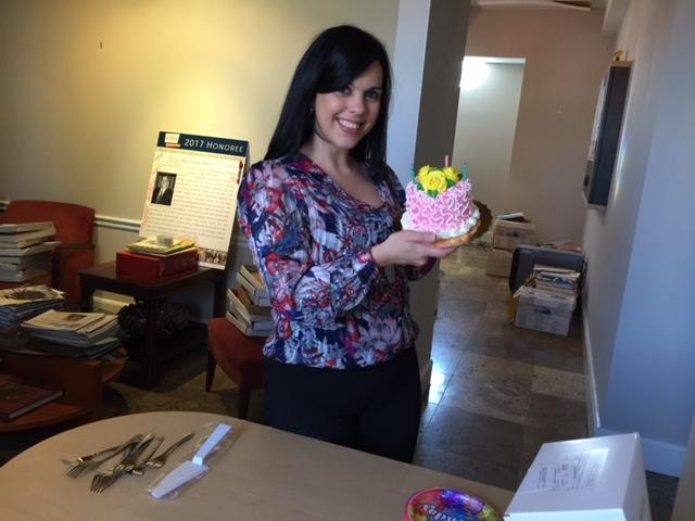 Yare, standing and holding a pink birthday cake with yellow flowers.