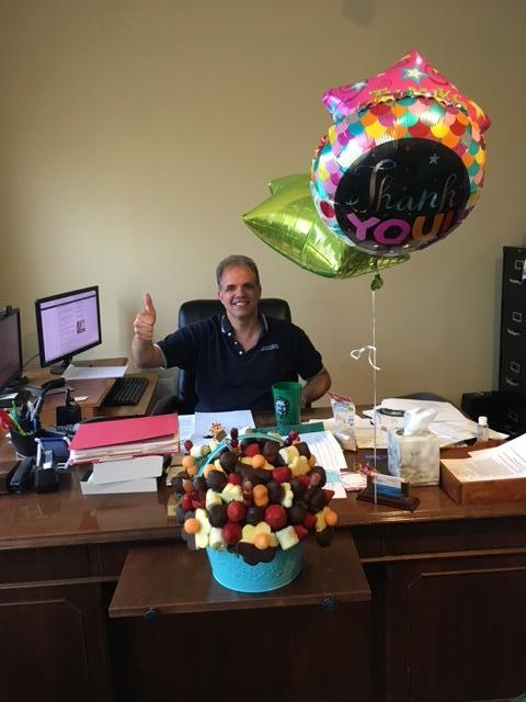 Matt sitting in his chair with his thumb up smiling with a fruit basket and balloons.
