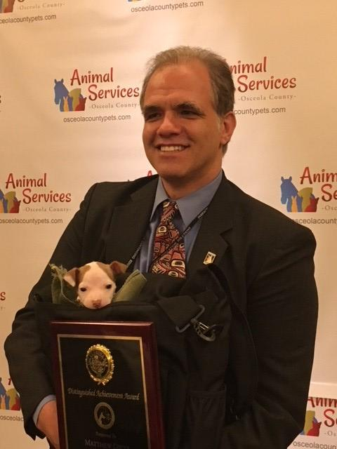 Matt showing off the animal law section award with pit bull puppy in a bag