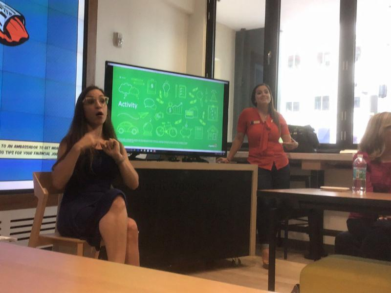 sign language interpreter sitting and interpreting at a financial training at capital one