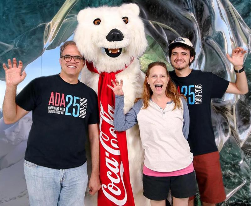 Debbie, Matt, and Max standing with the coca cola bear with their hands up like a bear claw.