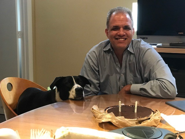 matt sitting with lucy with a pie and 2 candles.