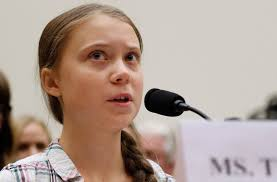 head shot of Greta Thunberg speaking into a microphone