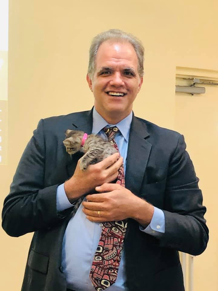 Matt smiling and holding a kitten during a cat cafe style CLE training