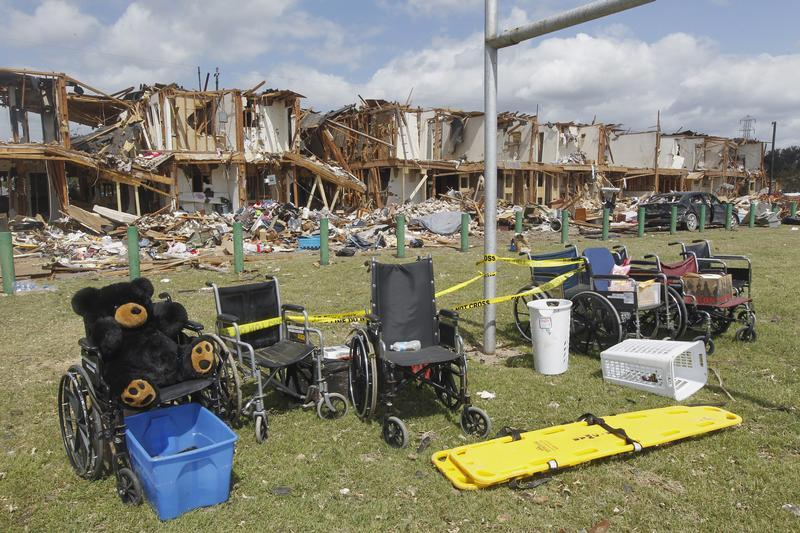 destroyed houses in the background with a line of empty wheelchairs in the front of the picture.