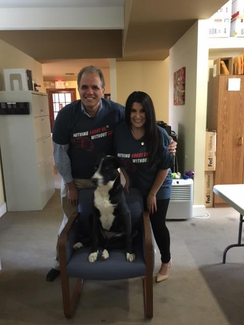 Matt and Lisa wearing NAD t-shirts with lucy sitting in a chair.