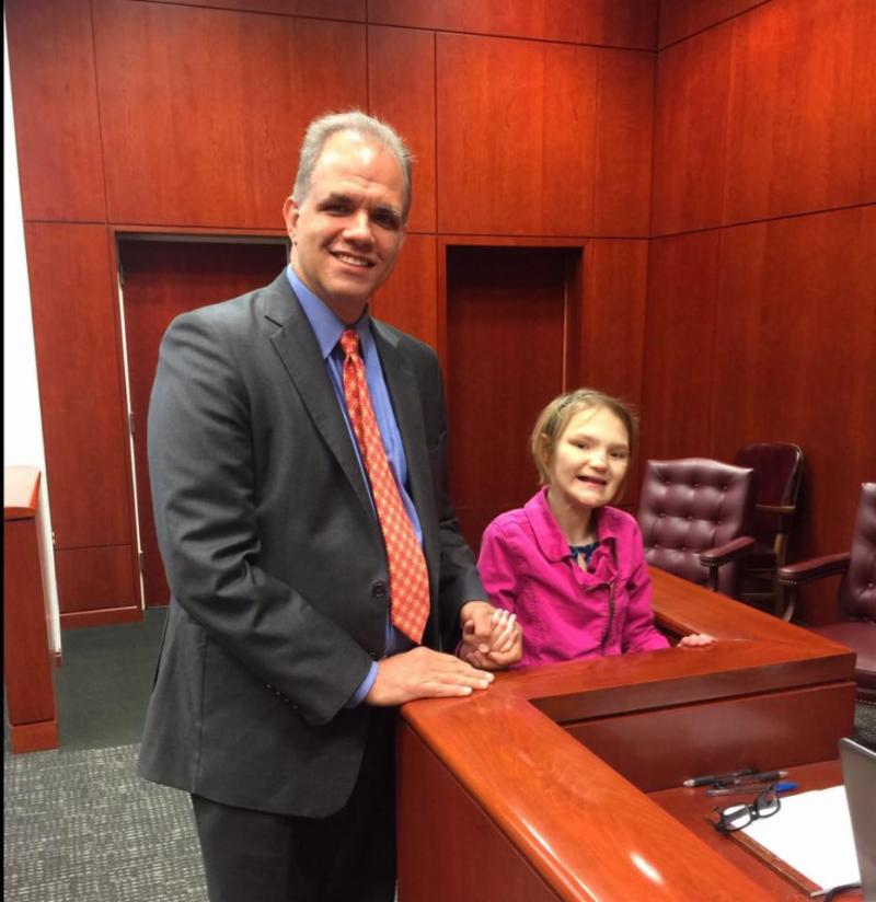 Matt Dietz and seven year old Kailea in pink by the witness stand in a courtroom