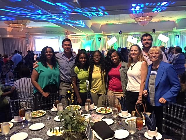 Unite Miami team standing at a table at the children's trust luncheon.  There are bright colors being projected on the ceiling and walls.