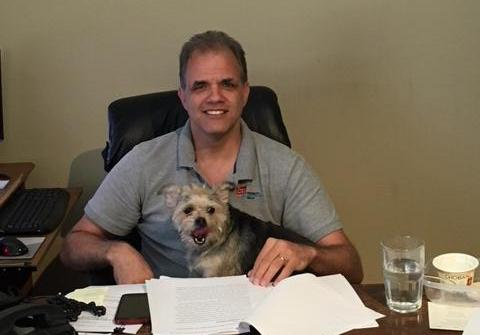Matt working at his desk with Murphee in his lap.
