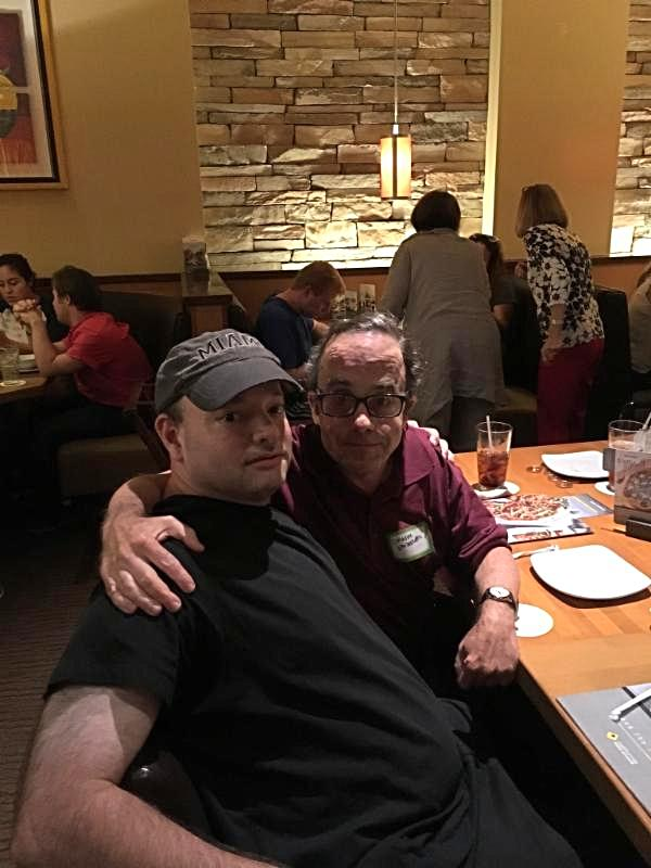 Eric and friend sitting having dinner.