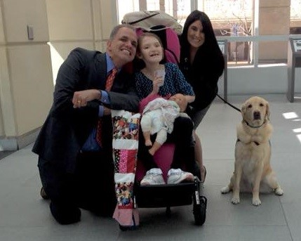 Lisa and Matt in the courthouse with Kailea and her service dog after a trial  The dog is a golden retriever and Kailea as a seven year old girl in a stroller