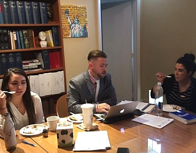 Interns Nia and Stephen with attorney Lisa working and eating ice cream in the conference room.