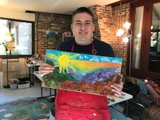 Ben holding a mixed media painting that he created the painting is a landscape with a big sun in the top left corner