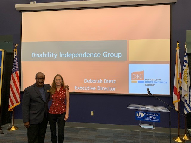 debbie and walter at miami dade college standing in front of a screen with dig logo in the background