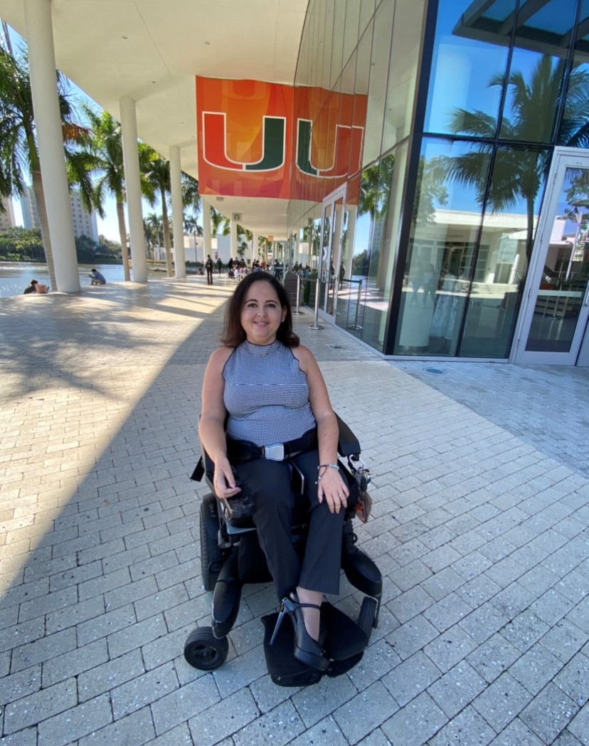 Lorinda at the University of Miami Campus with a big banner with a U on it