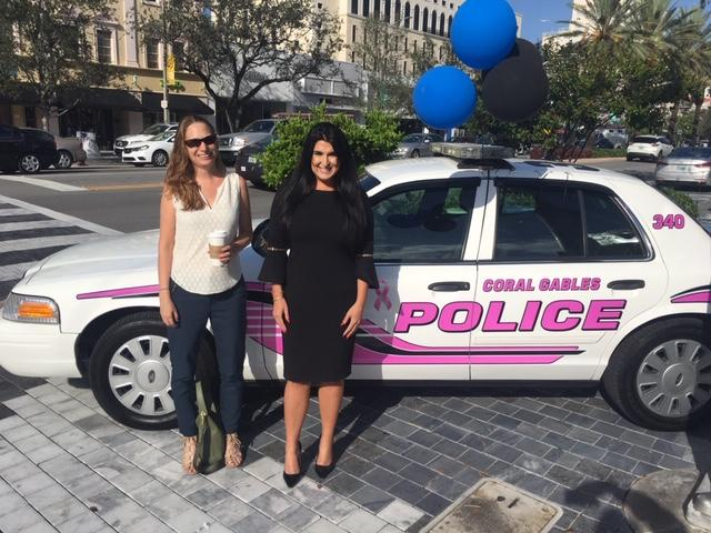Debbie and Lisa in front of a pink city of coral gables police car