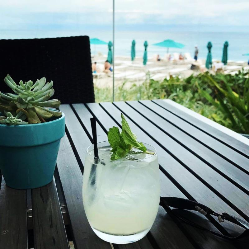 a mojito drink sitting on a table with the beach in the background.