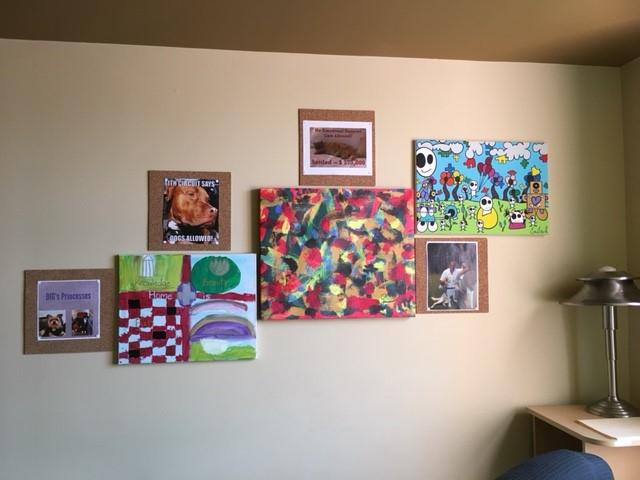 DIG office wall with paintings by persons with disabilities and pictures of our clients and their animals.