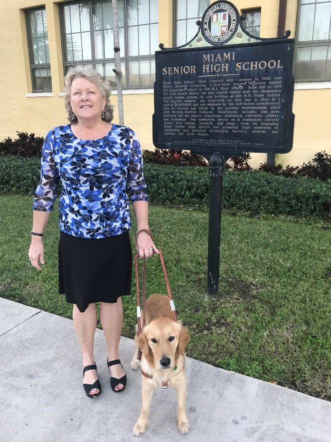 Jan standing with her dog in front of a sign for miami senior high school
