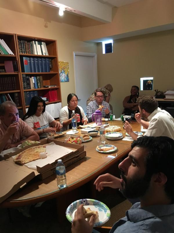 DIG staff and interns sitting a conference room table eating lunch.