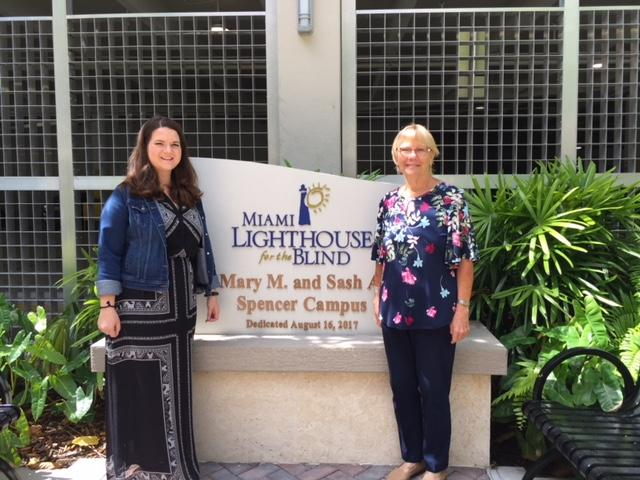 Kelly and Sharon standing next to the sign for Miami Lighthouse for the blink