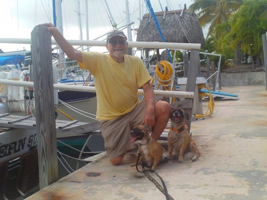 Mr Bishop kneeling with his two dogs on a dock in front of a boat