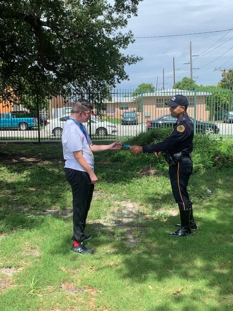 A student with a disability outside practicing using his wallet card with an officer
