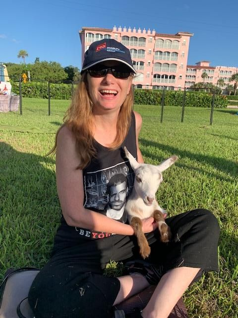 Debbie sitting outside and holding a white and brown goat