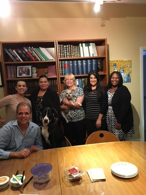 DIG staff in conference room with Murphee the dog and Lucy the dog.  Happy Administrative Professionals Day.