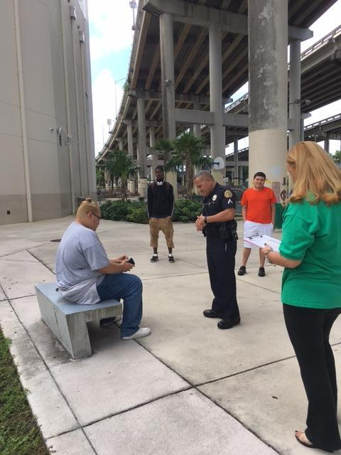 Polce officer speaking to a young man sitting on a bench.
