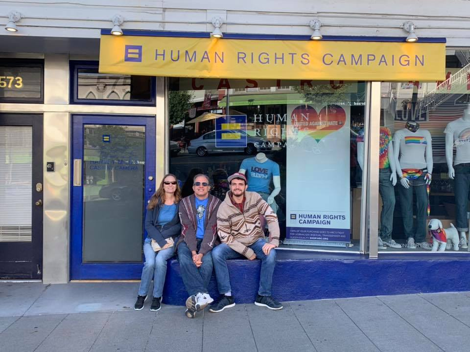 debbie matt and max sitting in front of a store front with a banner saying human rights campaign in the castro district of san francisco