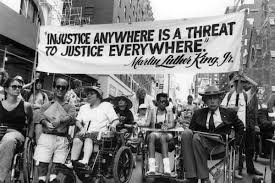 black and white photo of a protest with a diverse group of people both by race and ability holding a banner that says injustice anywhere is a threat to justice everywhere by MLK Jr