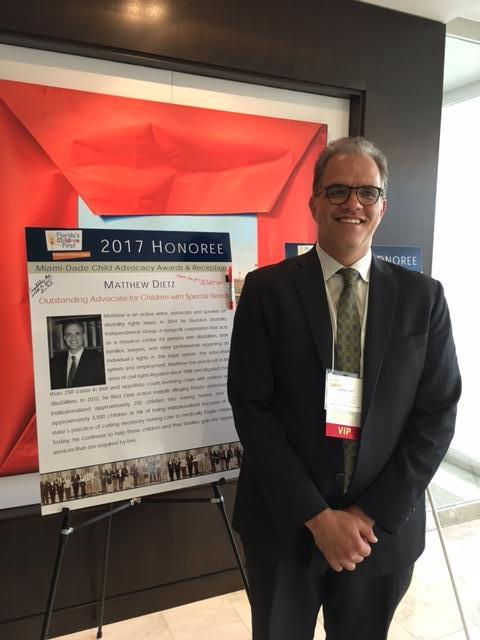 Matthew standing in front of the FCF poster as a 2017 Honoree.