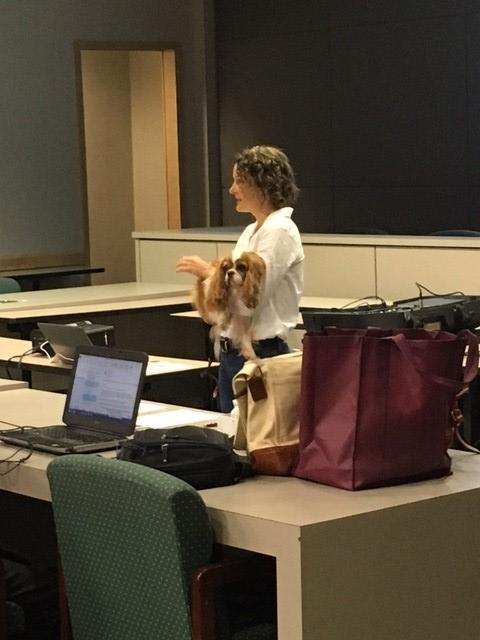 Stephanie Perkins Program DirectorTallahassee Memorial Animal Therapyholding a dog and speaking at the seminar.