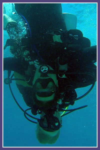 Polett SCUBA diving under the water upside down.