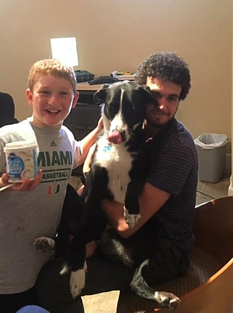 Michael, Max, and Lucy getting ready for an intern good bye ice cream party.  Michael is holding a can of frosting and Max is hugging Lucy.