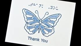 a card with thank you in braille with a blue butterfly