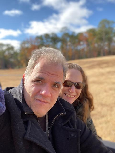 debbie and matt smiling with fall trees in the background