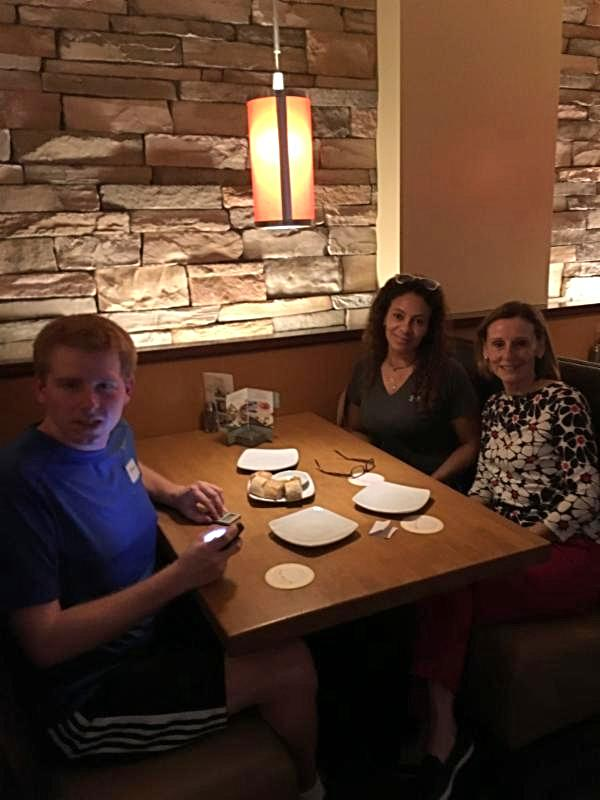Marie, Thomas, and his aid sitting in a both having dinner.