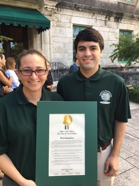 Erika and David standing and holding the proclamation outside Coral Gables City Hall.