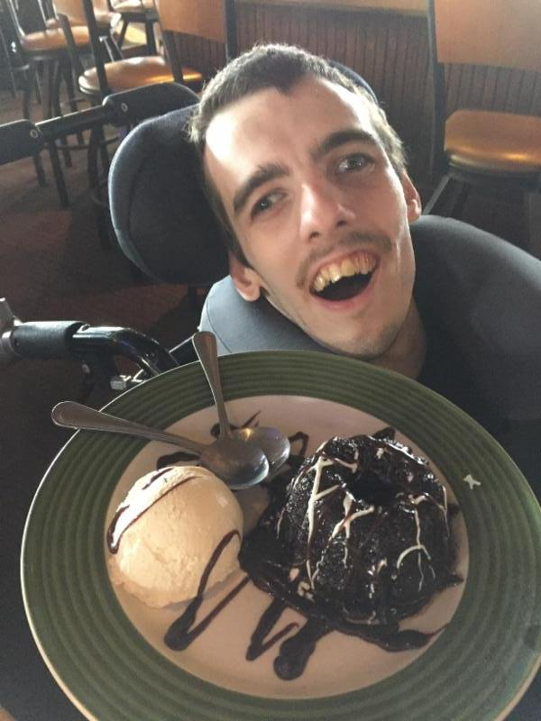 Nick smiling with a big plate of chocolate cake and vanilla ice cream in front of him.
