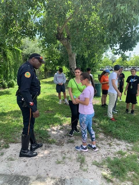 Claudia supervising an interaction outside between a student with a disability and an officer during a wallet card training